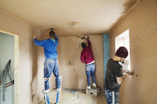 Plasterers working on house construction site
