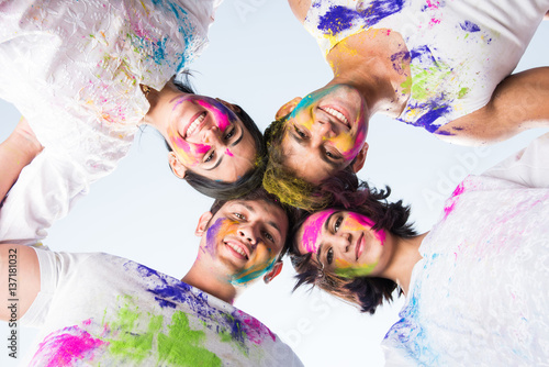 4 indian friends or 2 young couples celebrating Holi festival with sweets, bhang, pichkari and hands painted with gulal having copy space showing white board, isolated over white background
