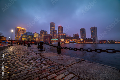 Sticker - View of Boston skyscrapers night and promenade.   The tops of the buildings in the fog and haze. Rainy foggy weather, brilliant paving and lights of skyscrapers.