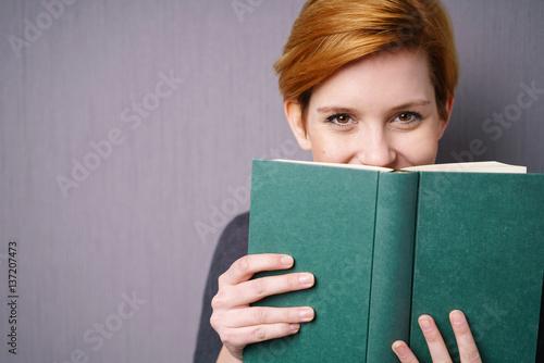 Fotografie, Obraz  lachende frau versteckt sich hinter einem buch