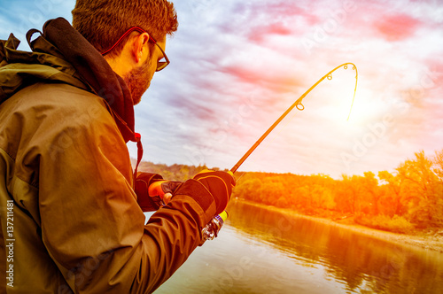 Foto op Aluminium Vissen Young man fishing on a river from the boat at sunset