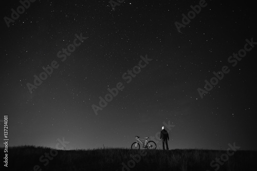 black and white art photography monochrome, starry sky, night photography, astrophotography, the silhouette of a man, a man standing next to a mountain bike on the background of a starry sky