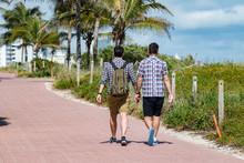 Gay Couple Walking On Miami Beach Promenade