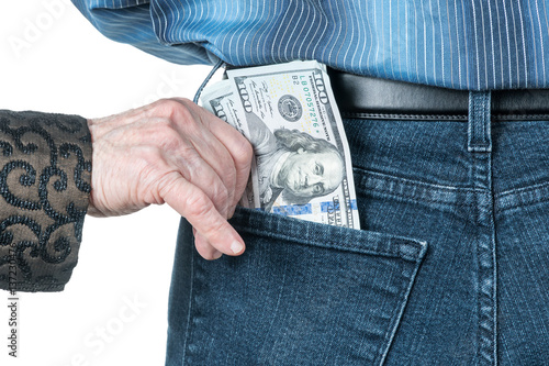Fotografía  Senile hand puts dollars in the back pocket of jeans strangers, isolated on a wh