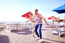 Couple Using Skateboard On Promenade