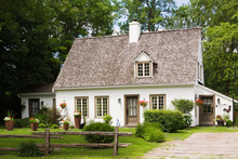 Old (circa 1886) White With Beige And Brown Trim Canadiana Cottage Style Home Facade In Summer, Quebec, Canada