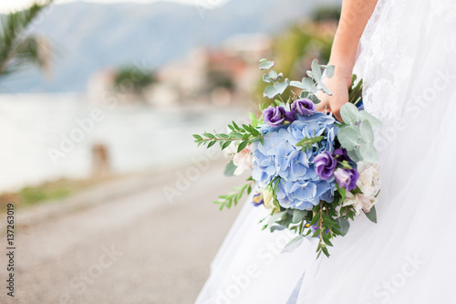 Bride Holds Wedding Bouquet From Blue Flowers Hydrangea And Stands