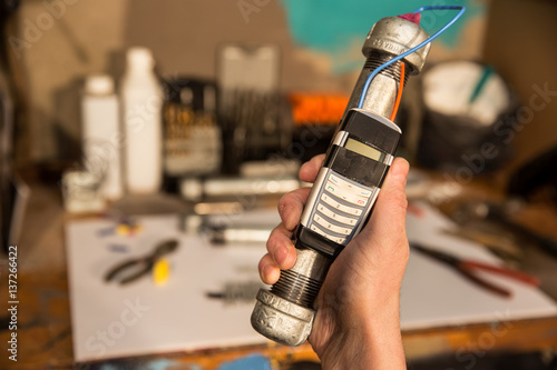 Fotografie, Obraz  Pipe bomb in hand with workshop in background