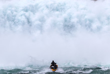 Jet Skier Riding Into A Giant Wall Of Water From A Dam Spillway