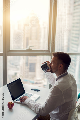Photo  Sideview of young man having short break drinking morning coffee.