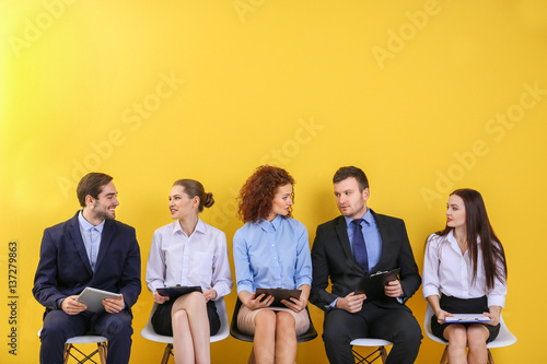 Group of people waiting for job interview on yellow wall background