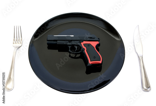 Fotografie, Tablou  Pistol gun toy in plate with fork and knife isolated on white background