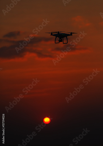 Foto op Canvas UFO flying drone quadrocopter at sunset