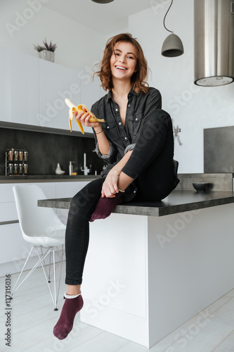 Happy woman sitting at kitchen eating banana indoors фототапет