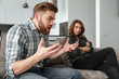 Angry quarrel loving couple sitting on sofa indoors