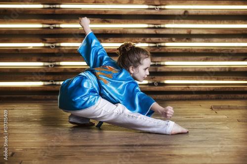 Plakat Całkiem mała dziewczynka w pokoju w sportowej odzieży dla sztuk walki to Wushu