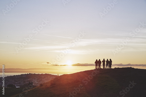 People watching sunrise over city