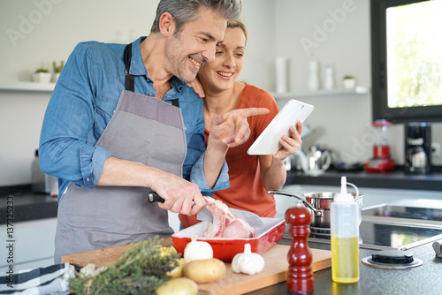 Poster Cuisine Couple in home kitchen using electronic tablet