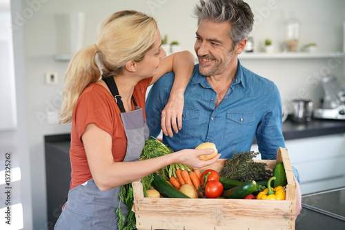 Poster Cuisine Portrait of couple in domestic kitchen holding basket of fresh vegetables