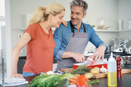 Keuken foto achterwand Koken Middle-aged couple having fun cooking together in home kitchen