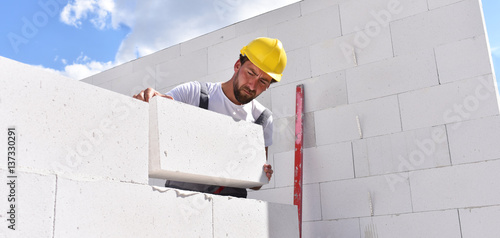 Fotografia, Obraz  Maurer auf einer Baustelle - Neubau eines Einfamilienhauses