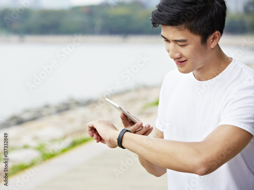 Photo  young asian man checking cellphone and watch before exercise