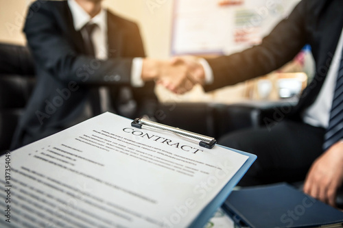 Fototapeta Close-up of business contract with pen at workplace on background of office workers interacting. Firm handshake between two colleagues after signing a contract. obraz