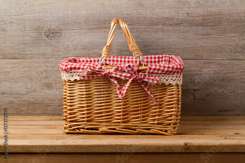 Fotografija  Picnic basket with checked cloth on table over wooden wall background