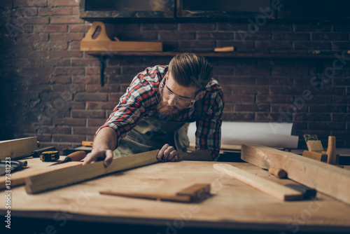 Obraz Bearded handsome cabinetmaker at the tabletop with tools.  Stylish craftsman with brutal hairstyle and saved glasses holding woodenplank at his workstation - fototapety do salonu
