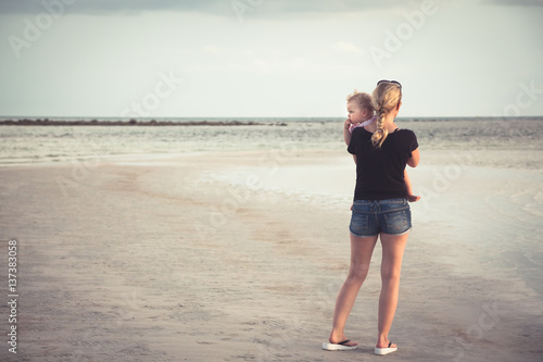 Fotografie, Obraz  Single mother with baby on her hands looking into the distance at horizon over sea at beach with copy space