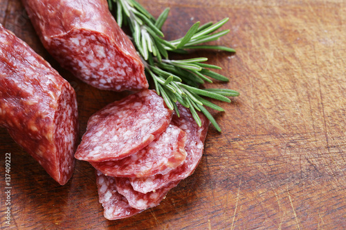 Valokuva salami sausage with rosemary on a wooden board
