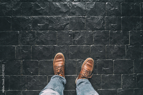 Man Leg With Brown BootsBlack Stone Floor TextureSelective Focus On Boots