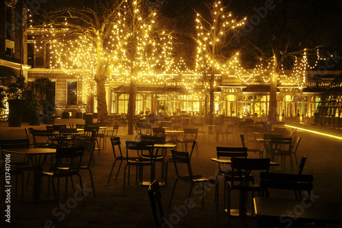 Staande foto Marokko empty night restaurant, lot of tables and chairs with noone, magic fairy lights on trees like christmas celebration