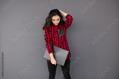 young woman on grey background standing and holding laptop - Buy