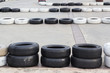 waste automotive rubber wheels for racing track on cement floor, yellow and white old tires for car racing track
