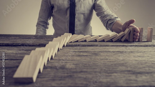 Fotografía  Businessman preventing dominoes from crumbling with palm