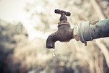 A faucet with a water drop / Water consumption concept