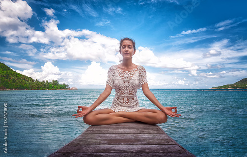 Young beautiful healthy woman making meditation on the beach