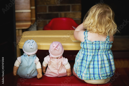 A toddler sits at a play table with her two dolls; Alberta, Canada Poster