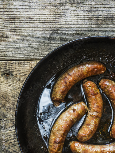 Fried homemade sausages in pan on old weathered wooden table; Kiev, Ukraine