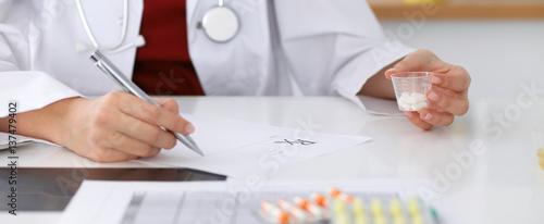 Photo  Female medicine doctor fills up  prescription form to patient closeup