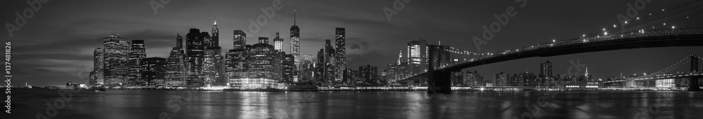 Fototapeta New York city with Brooklyn Bridge, iconic skyline panorama at night in black and white