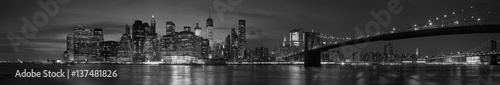 Deurstickers New York New York city with Brooklyn Bridge, iconic skyline panorama at night in black and white