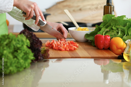 Fotobehang Koken Closeup of human hands cooking vegetables salad in kitchen on the glassr table with reflection. Healthy meal and vegetarian concept