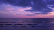 Aerial drone flying over a desert beach at the sunset purple sky