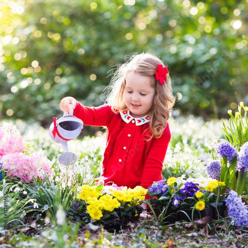 Papiers peints Pansies Kids plant and water flowers in spring garden