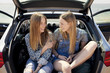 Two girlfriends sitting in car trunk at beach