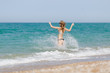 Tall slim young woman rushes into the sea