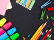 school supplies pencils, markers, buttons, colored paper on a black background