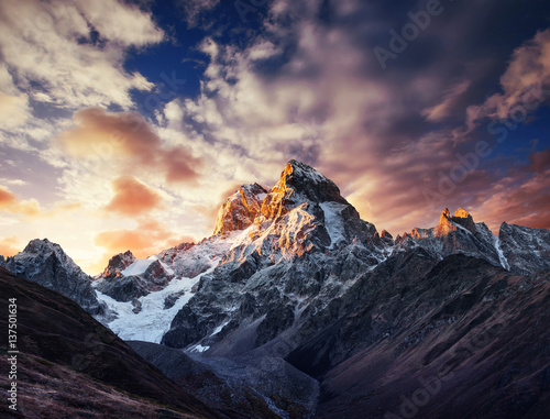 Autumn landscape and snow mountains in beautiful cumulus clouds. Wall mural